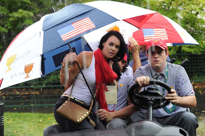Amanda Dufner sits on husband Jason Dufner as they seek shelter from the rain during the Day Two fourball matches.