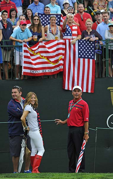 Fred Couples and girlfriend Nadine Moze pose with fans on the first tee during Day Three foursome matches.