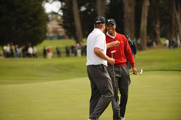 Tiger Woods and Steve Stricker put the first point on the board for the U.S., beating Geoff Ogilvy and Ryo Ishikawa.