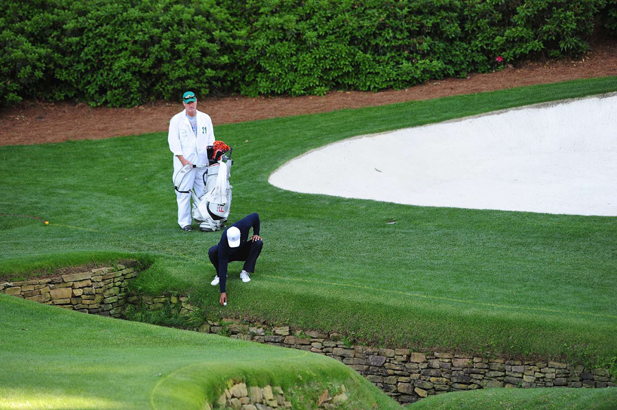 Woods went for the green in two on the par-5 13th, but his ball plugged in the hazard.
