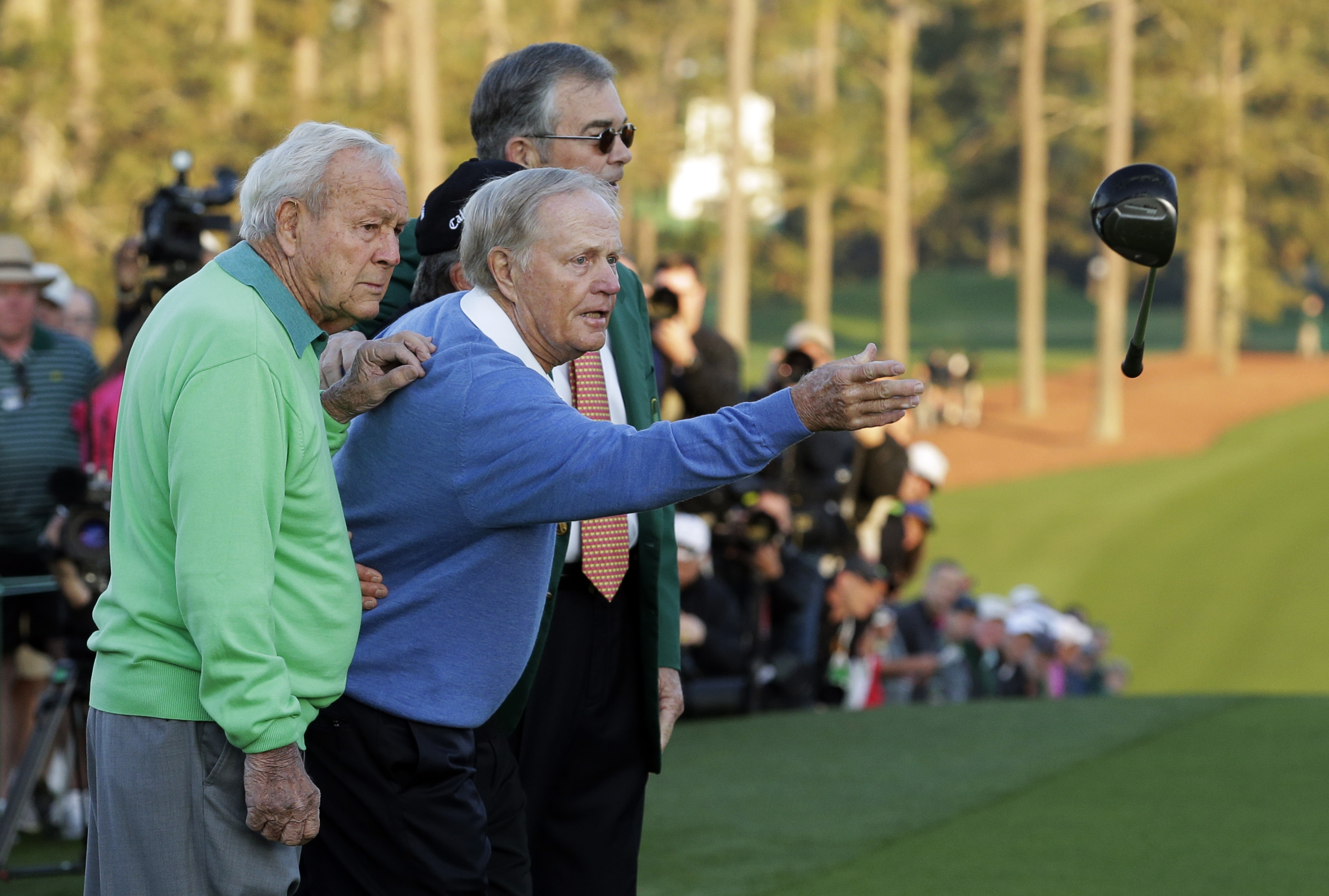 Jack Nicklaus, center, throws his driver while posing for photos with Arnold Palmer and Billy Payne, Chairman of the Augusta National Golf Course after hitting ceremonial drives on the first tee during the first round of the Masters golf tournament