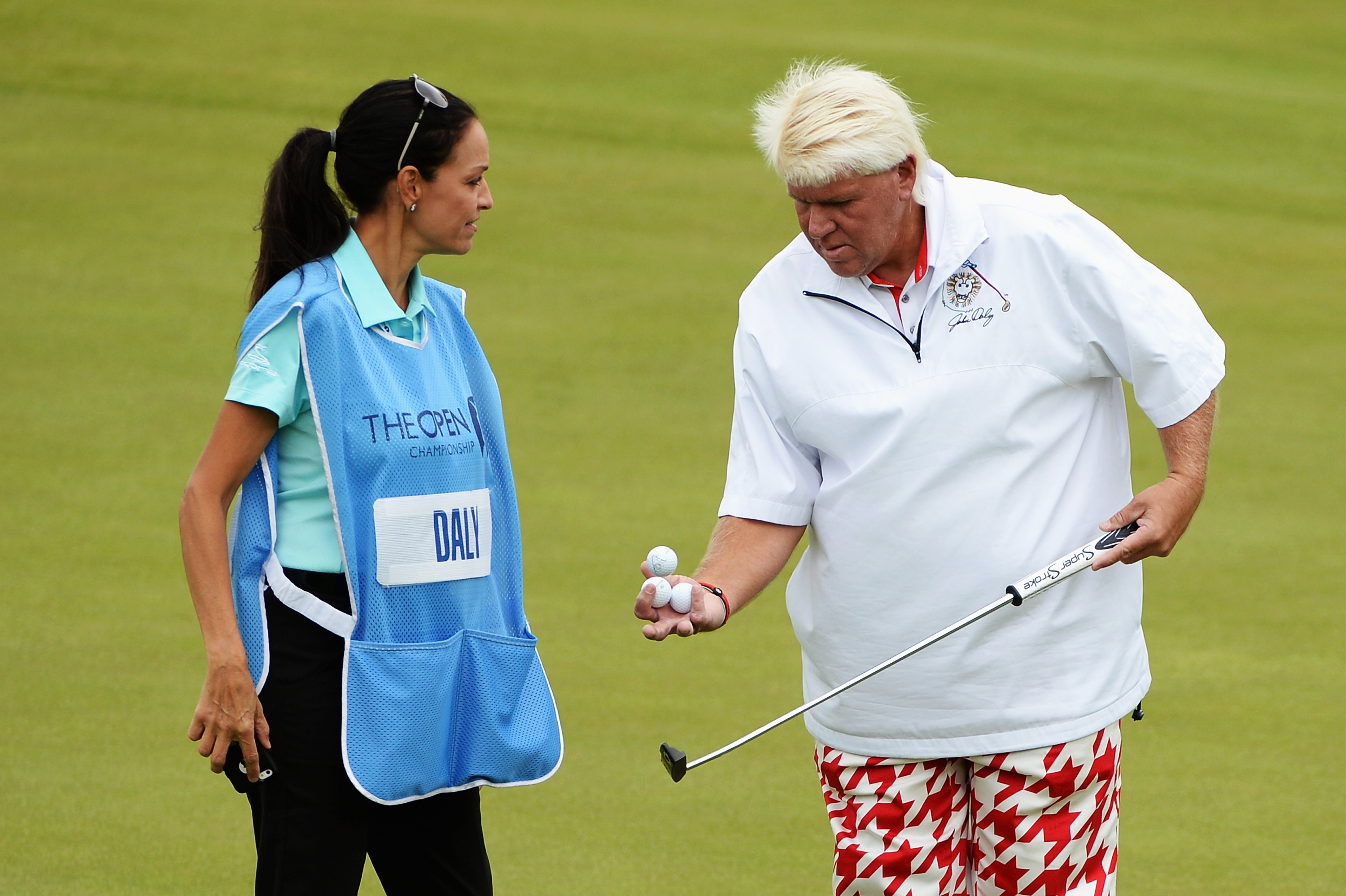 John Daly talks with Anna Cladakis, his girlfriend at the time, during a practice round prior to the start of the 2014 Open Championship.