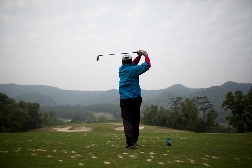 A golfer tees off on a golf course at Mission Hills Dongguan in China's Guangdong province.