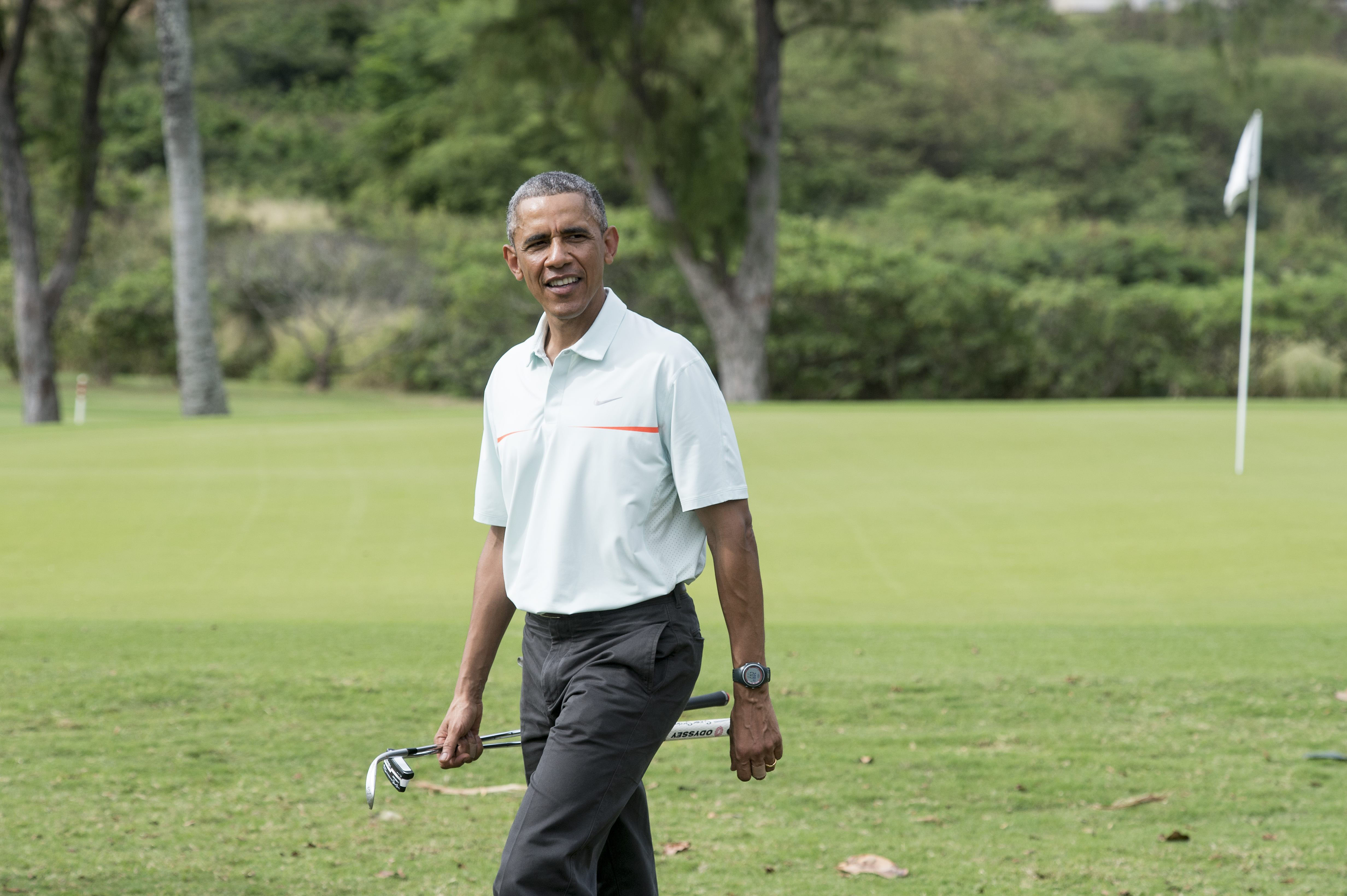 President Barack Obama talks to reporters as he plays golf with Malaysian Prime Minister Najib Razzak.