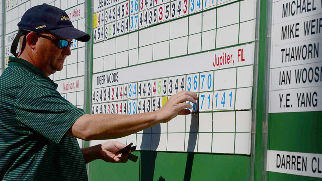 A scoreboard operator delivers the news of Tiger's 8 to Augusta National patrons.
