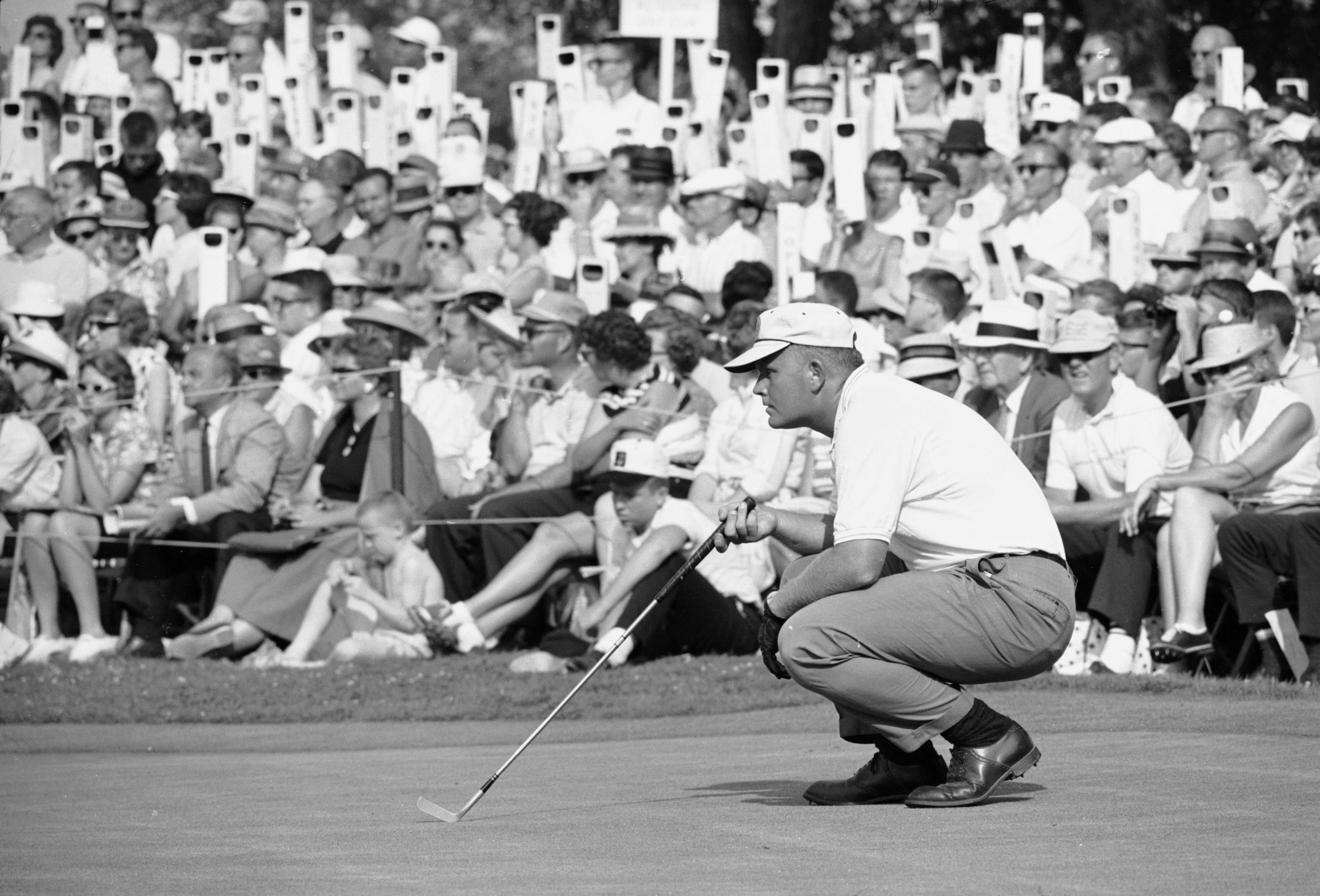 Watched by fans, American professional golfer Jack Nicklaus croches down to line up a shot during the 1962 U.S. Open.