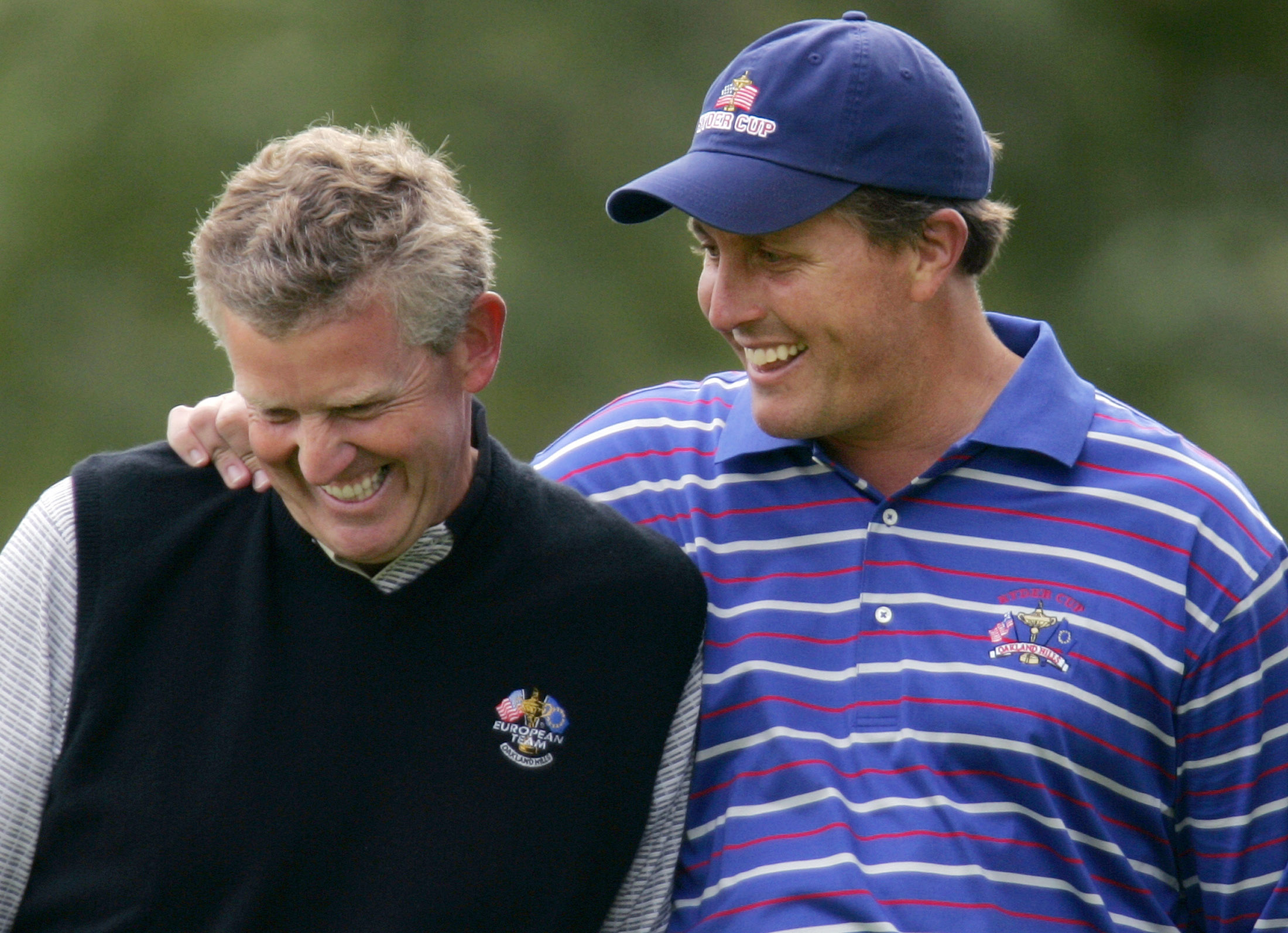 U.S. Ryder Cup golfer Phil Mickelson (R) shares a laugh with European golfer Colin Montgomerie, from Scotland, on the seventh green during their first round four-ball match at the 35th Ryder Cup Matches in Bloomfield, Michigan, September 17, 2004.