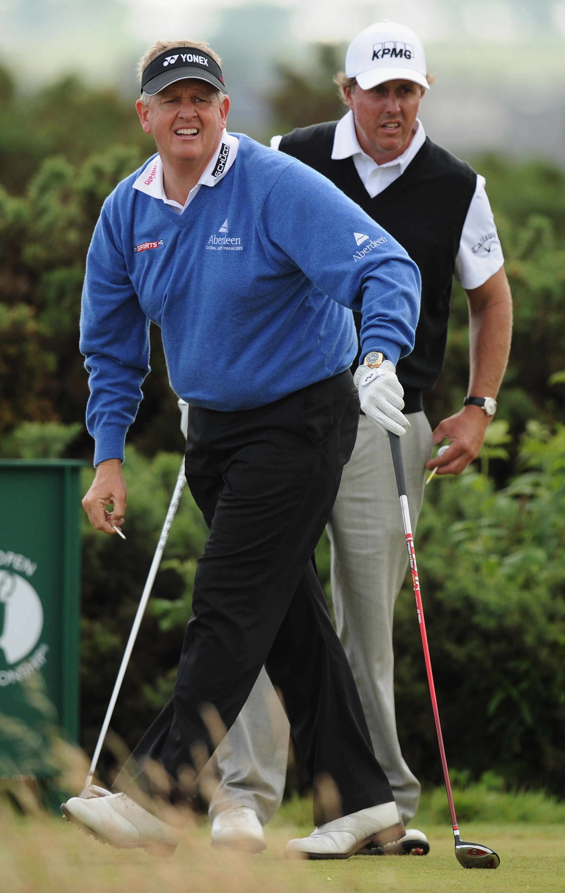 Colin Montgomerie of Scotland (L) watches his tee shot on the tenth hole as Phil Mickelson of the USA looks on during the second round of the 139th Open Championship on the Old Course, St Andrews on July 16, 2010 in St Andrews, Scotland.