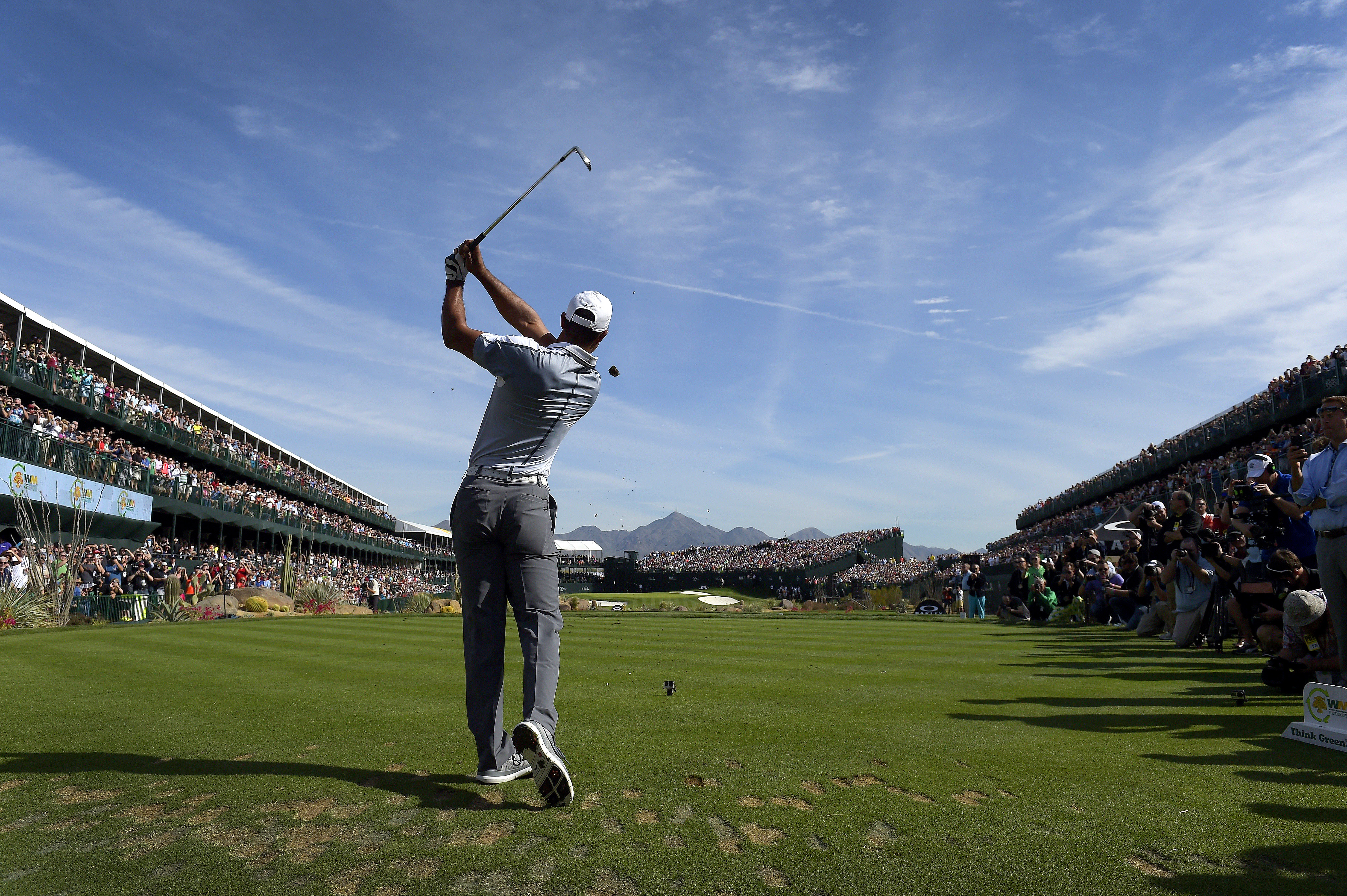 Tiger Woods tees off on the par-3 16th hole at TPC Scottsdale during a practice round prior to the 2015 Phoenix Open.
