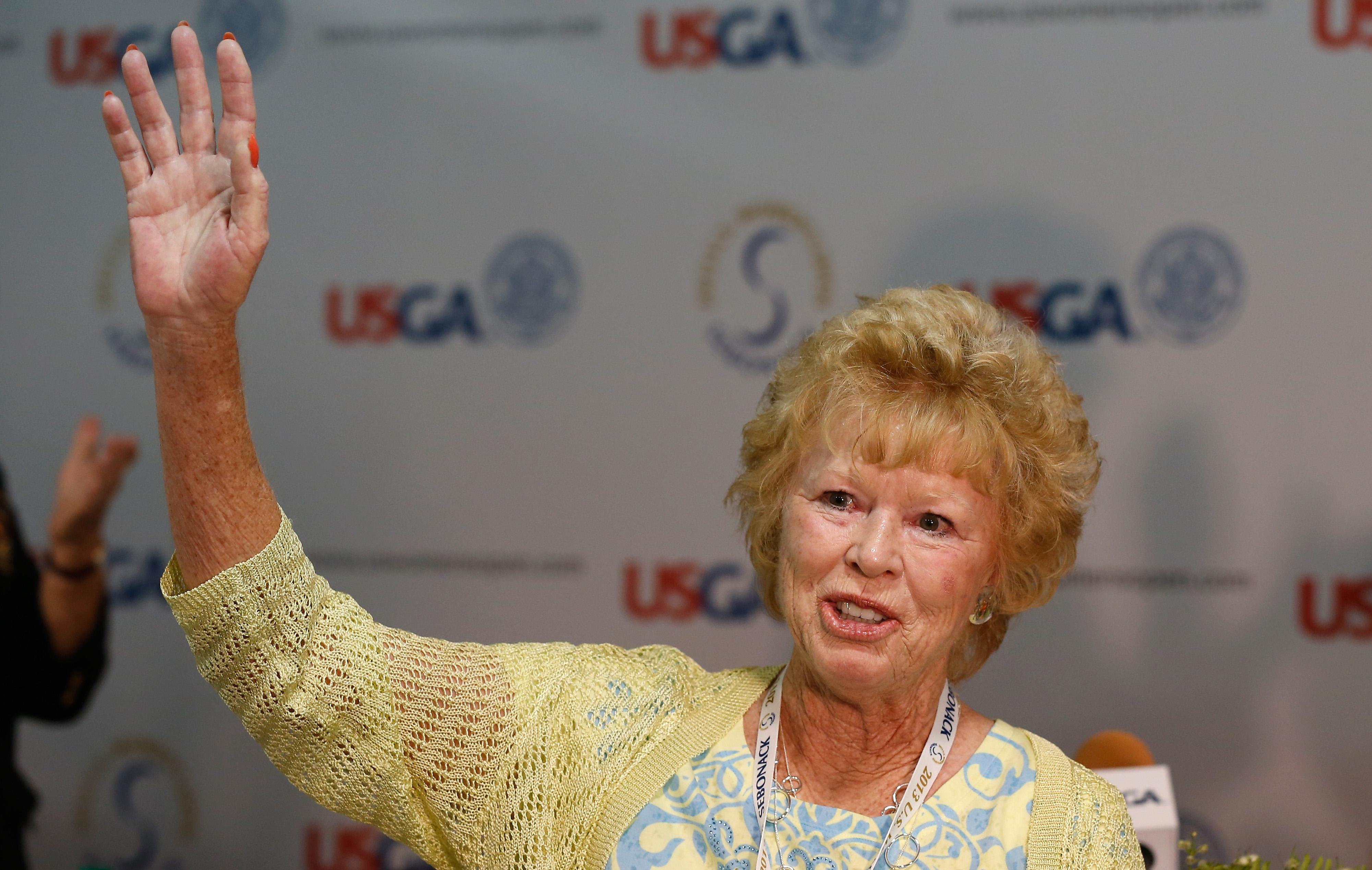 Rhonda Glenn, 67, who retired in May after nearly 50 years as a journalist and an employee of the United States Golf Association. waves to friends and the media prior to the start of the 2013 U.S. Women's Open.