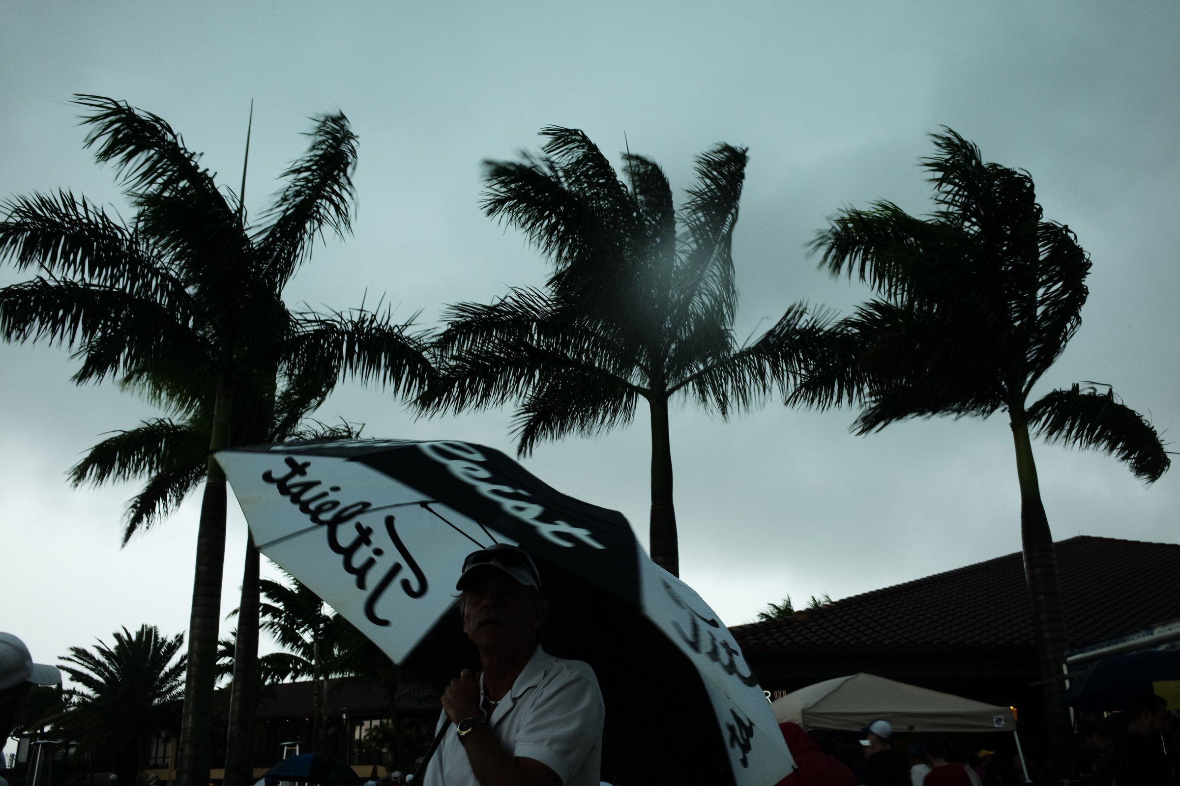An umbrella struggles to keep its shape in heavy winds at the Honda Classic on Saturday.