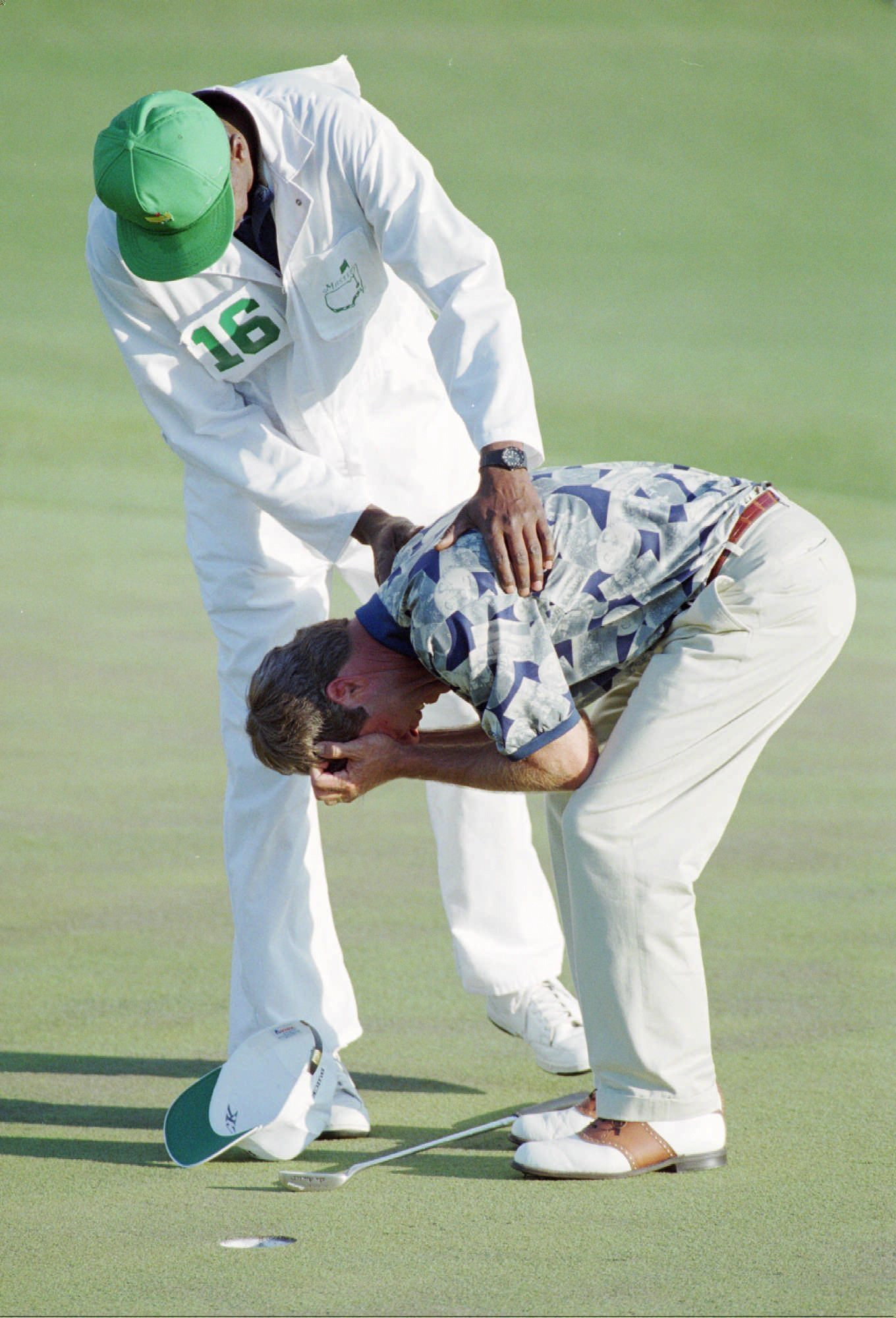 Masters champion Ben Crenshaw is consoled by caddy Carl Jackson on the 18th hole during the final round. Crenshaw's instructor Harvey Penick had died the previous Sunday.