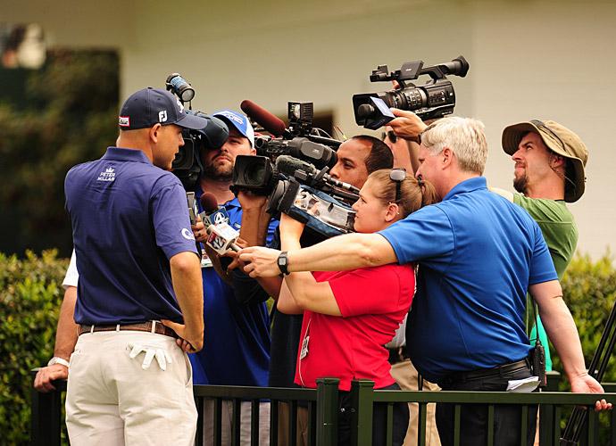 Bill Haas talks to a media scrum near the practice area.