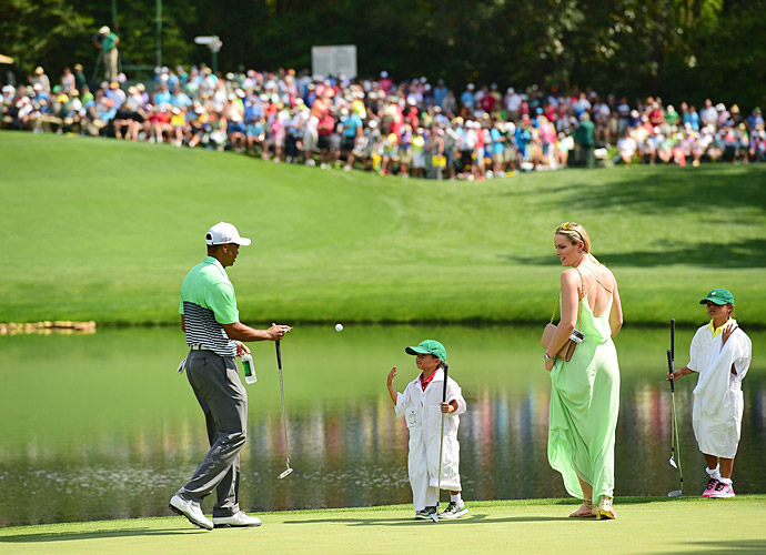 Charlie tosses a ball to Tiger as a professional Tour caddie would.