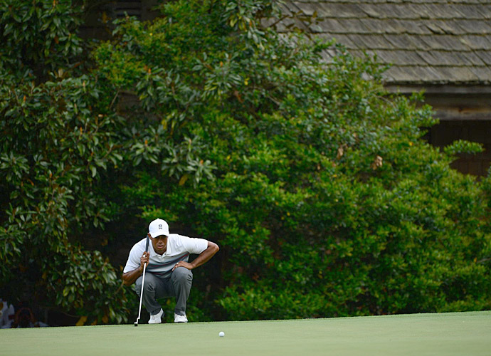 Woods lines up a putt during the first round.