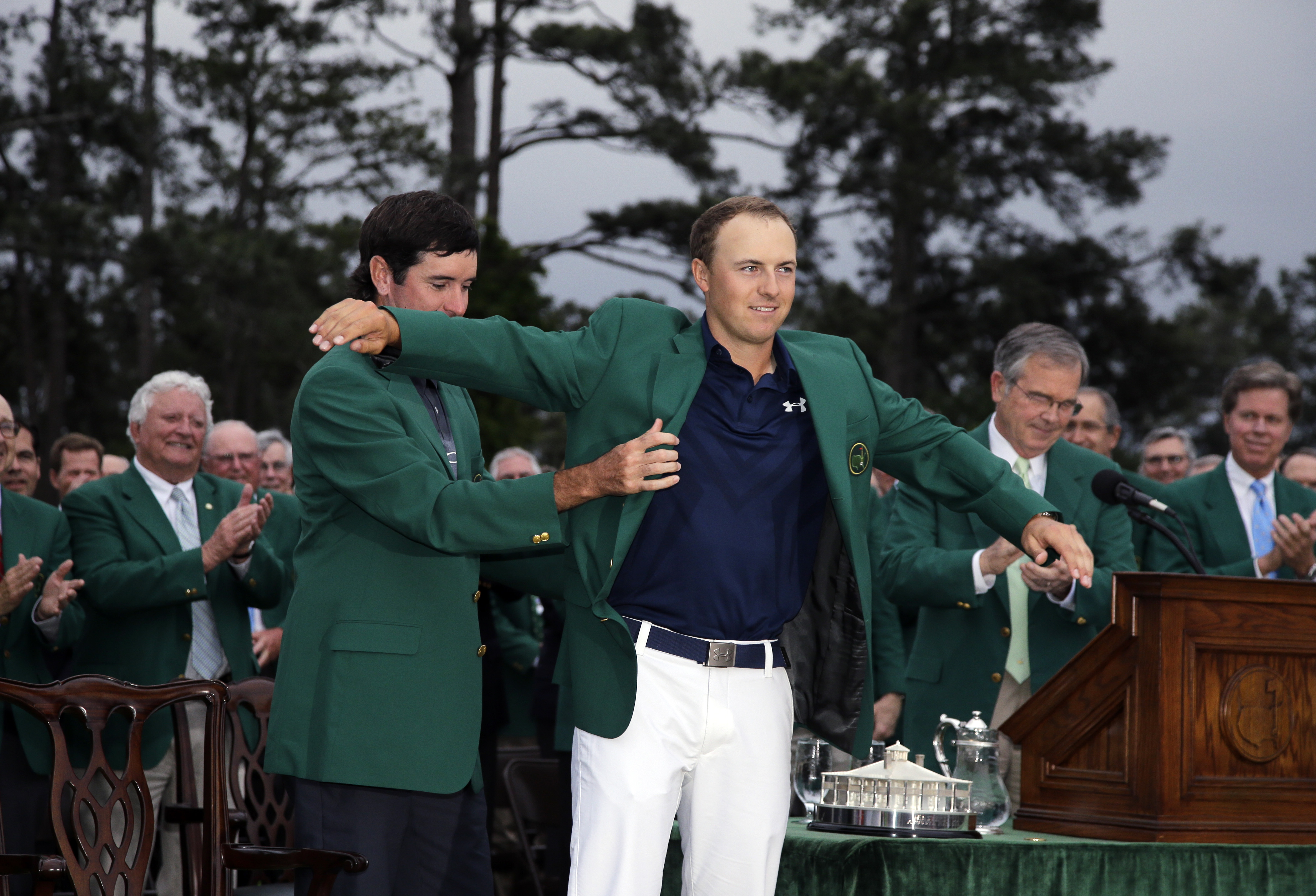 Bubba Watson helps Jordan Spieth put on his green jacket after winning the Masters golf tournament Sunday, April 12, 2015, in Augusta, Ga.