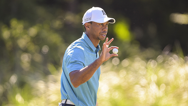 Tiger Woods waves his ball to fans after playing on the 14th hole green during the second round of THE PLAYERS Championship.