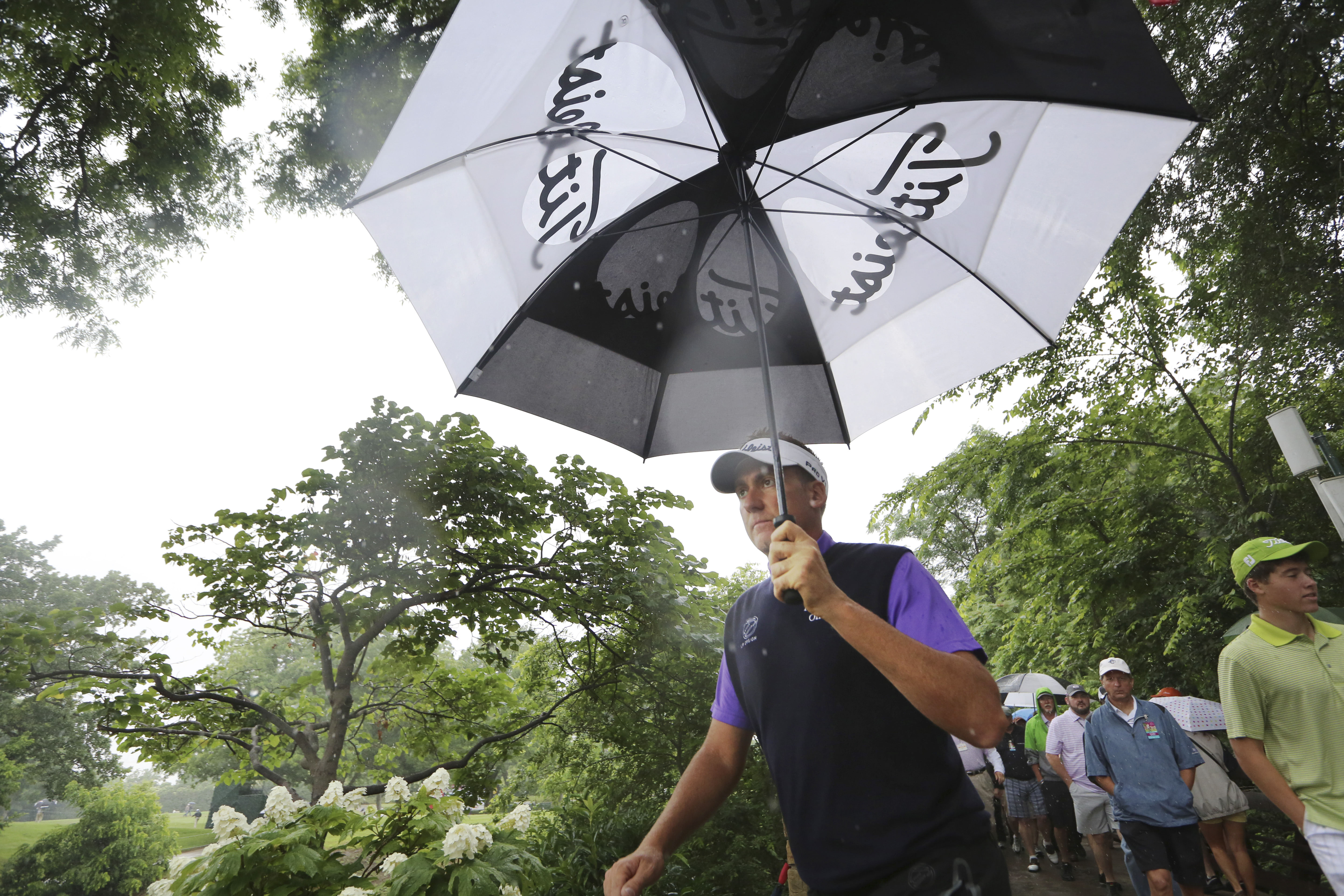 Ian Poulter uses an umbrella while walking the ninth hole during the second round of the Colonial golf tournament on Friday.