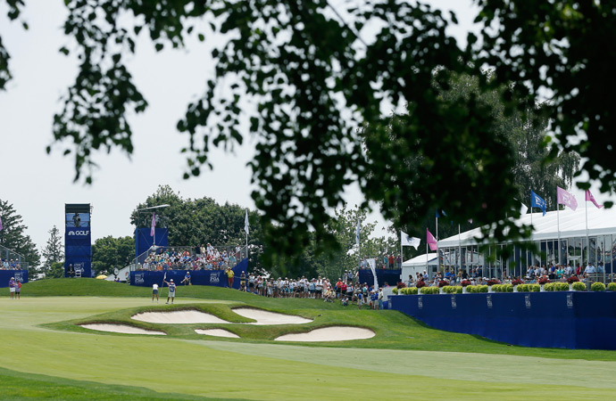 Fans watch the action by the 18th green on Friday.