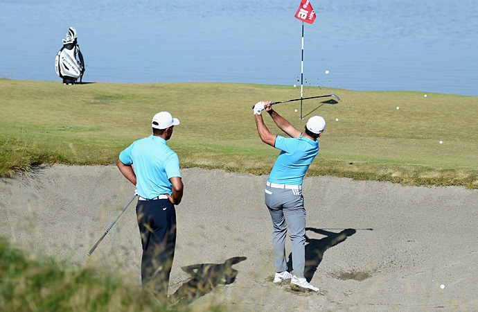 Jason Day practices bunker shots on Monday with Tiger Woods looking on.