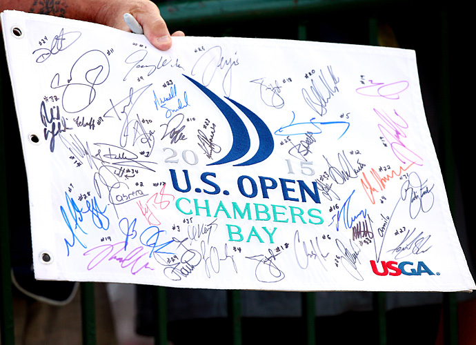 A fan holds a U.S. Open flag covered in players' signatures.