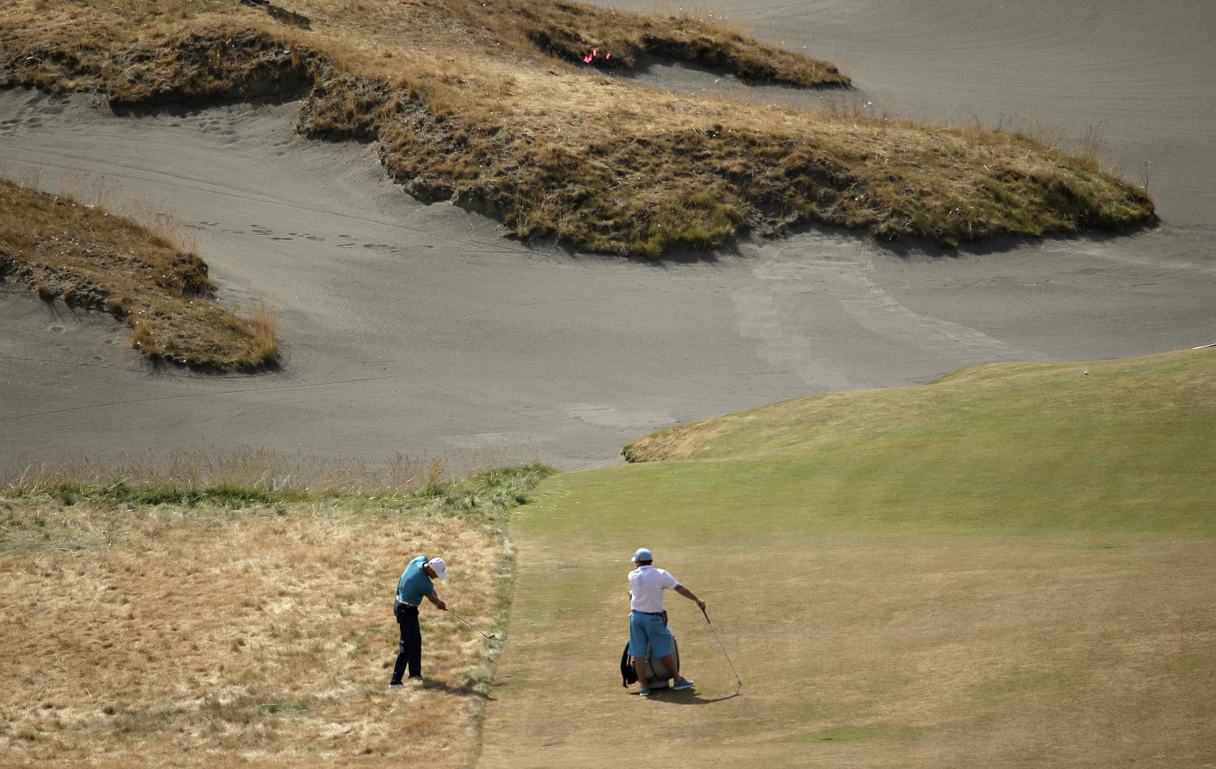 Martin Kaymer, left, of Germany, hits from rough on the fifth hole during a practice round for the U.S. Open golf tournament at Chambers Bay on Tuesday, June 16, 2015 in University Place, Wash. (AP Photo/Charlie