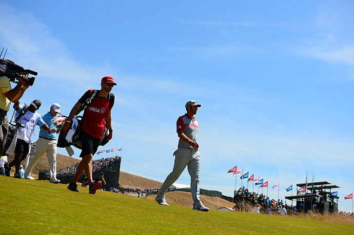 Dustin Johnson walks to the first tee to begin his third round.