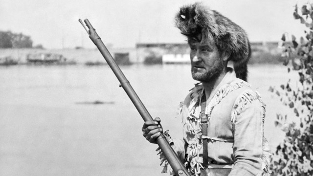 A man wearing a Davy Crockett outfit with a coonskin cap and a musket, circa 1928.