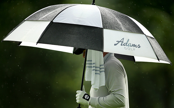 Robert Garrigus walks under his umbrella on the second hole during the second round of the Greenbrier Classic.
