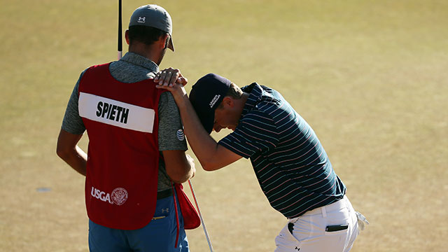 Jordan Spieth leans on his caddie Michael Greller after a birdie on the 18th green during the final round of the 115th U.S. Open Championship at Chambers Bay on June 21, 2015 in University Place, Washington.