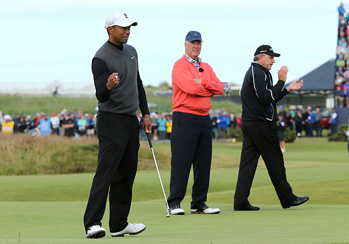 Tom Weiskopf looks on as Tiger Woods celebrates a putt during the Champion Golfers' Challenge on St. Andrews on Wednesday.