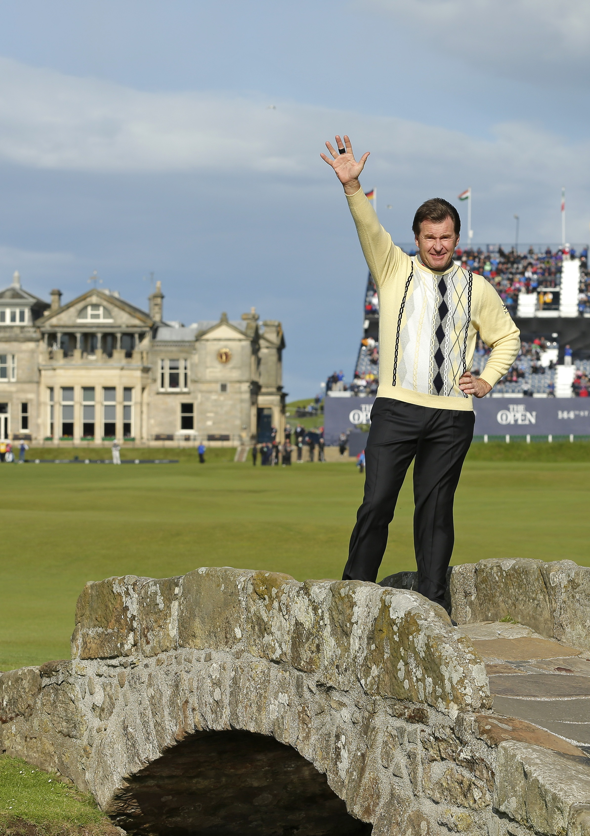 England's Nick Faldo waves as he poses for photographers on the Swilcan Bridge during the second round of the British Open at the Old Course at St. Andrews on Friday.