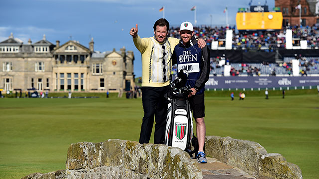 Sir Nick Faldo waves to the crowd as he stands on Swilcan Bridge with his son and caddie Matthew Faldo during the second round of the 144th Open Championship at The Old Course on July 17, 2015 in St Andrews, Scotland.