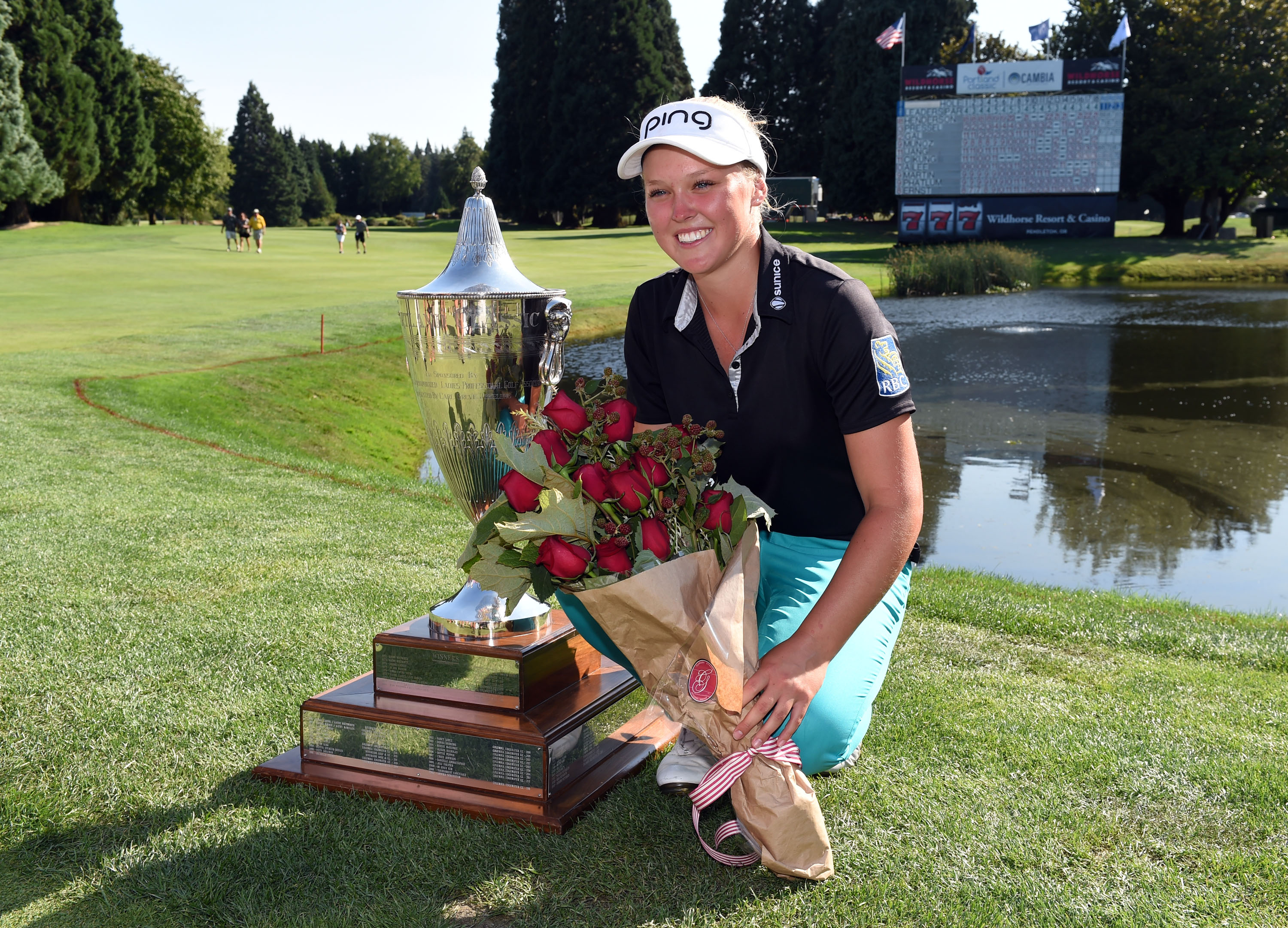 Brooke Henderson, of Canada, poses with the trophy on the 18th hole after winning the Cambia Portland Classic in Portland, Oregon, on Sunday.