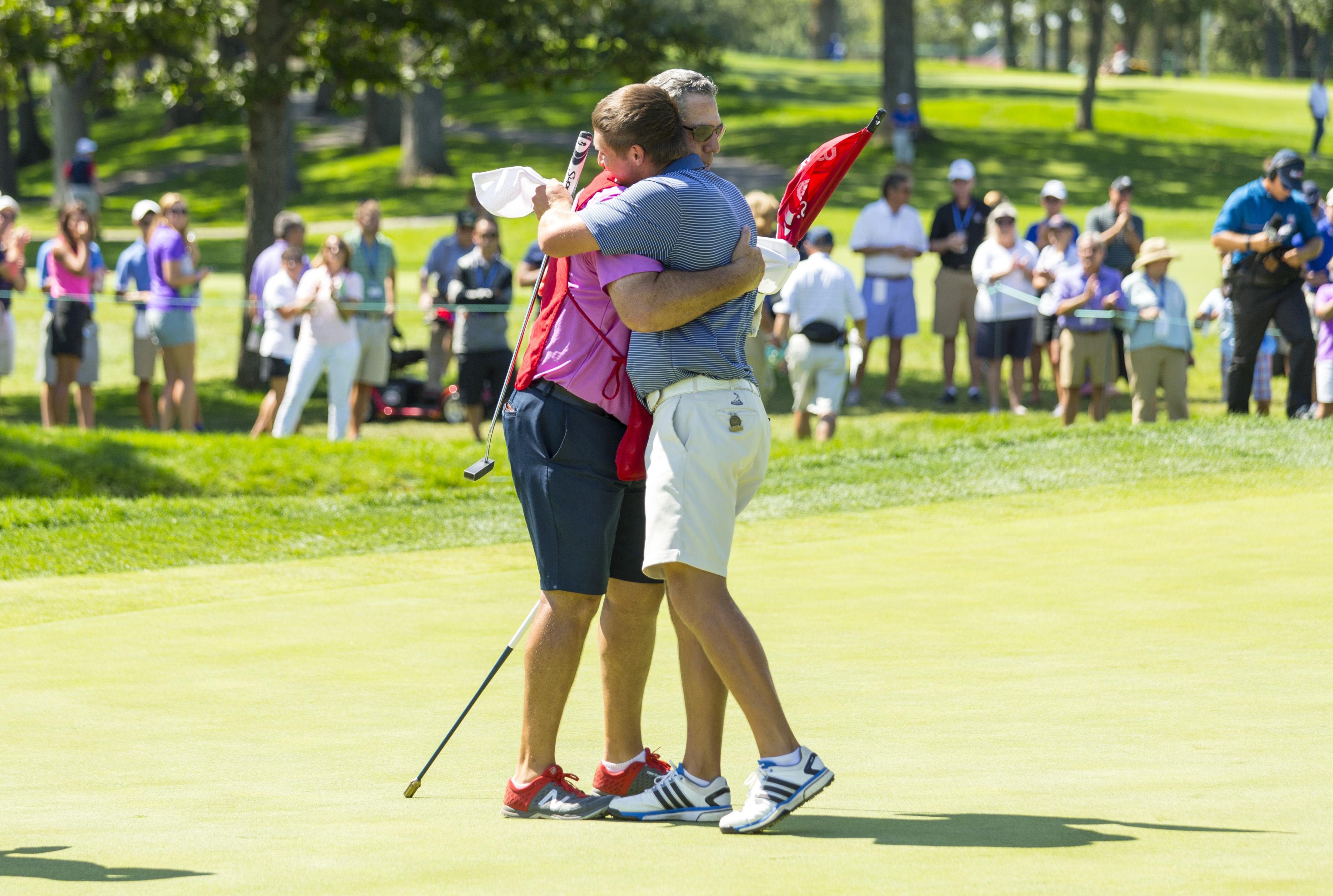 In this image provided by the United States Golf Association, Bryson DeChambeau, right, shares a hug with his caddie Mike Schy after winning his match 4 and 3 against Sean Crocker in the semifinal round of match play at the U.S. Amateur golf