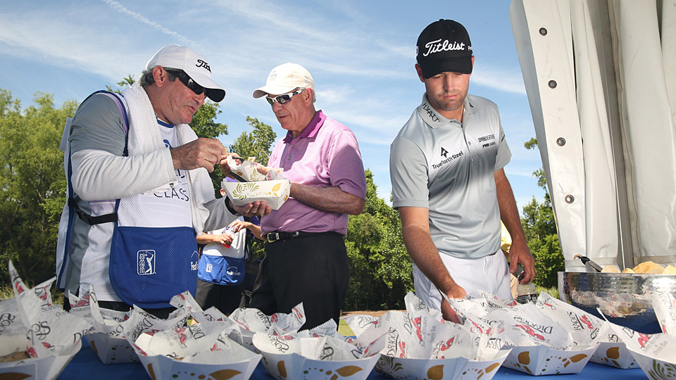 Tour pro Robert Streb tries some oysters at the 10th tee during the Zurich Classic Pro-Am.