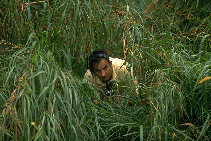 1997 Doral Ryder Open: CBS announcer David Feherty alone, looking through tall grass during second round.