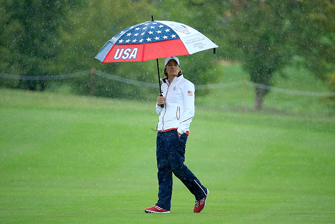 Juli Inkster, the United States Team captain, shields herself from the rain on the 12th hole during the Friday afternoon fourball matches.