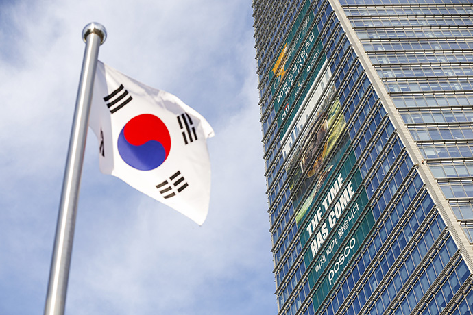A South Korean flag flies next to a large Presidents Cup banner displayed on the Northeast Asia Trade Tower (NEATT), the country's tallest building, prior to the start of The Presidents Cup.