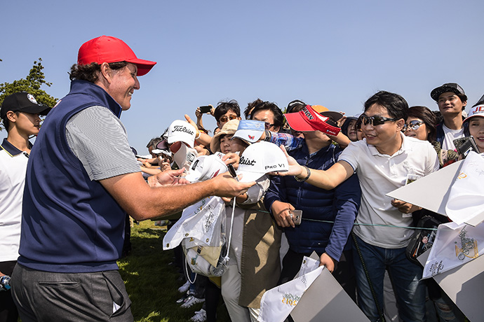Phil Mickelson signs autographs for fans during a Presidents Cup practice round.