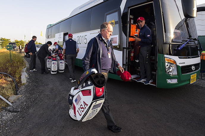 Team USA Captain Jay Haas carries the bag of Captain's Assistant Davis Love III before group photos were taken during practice.