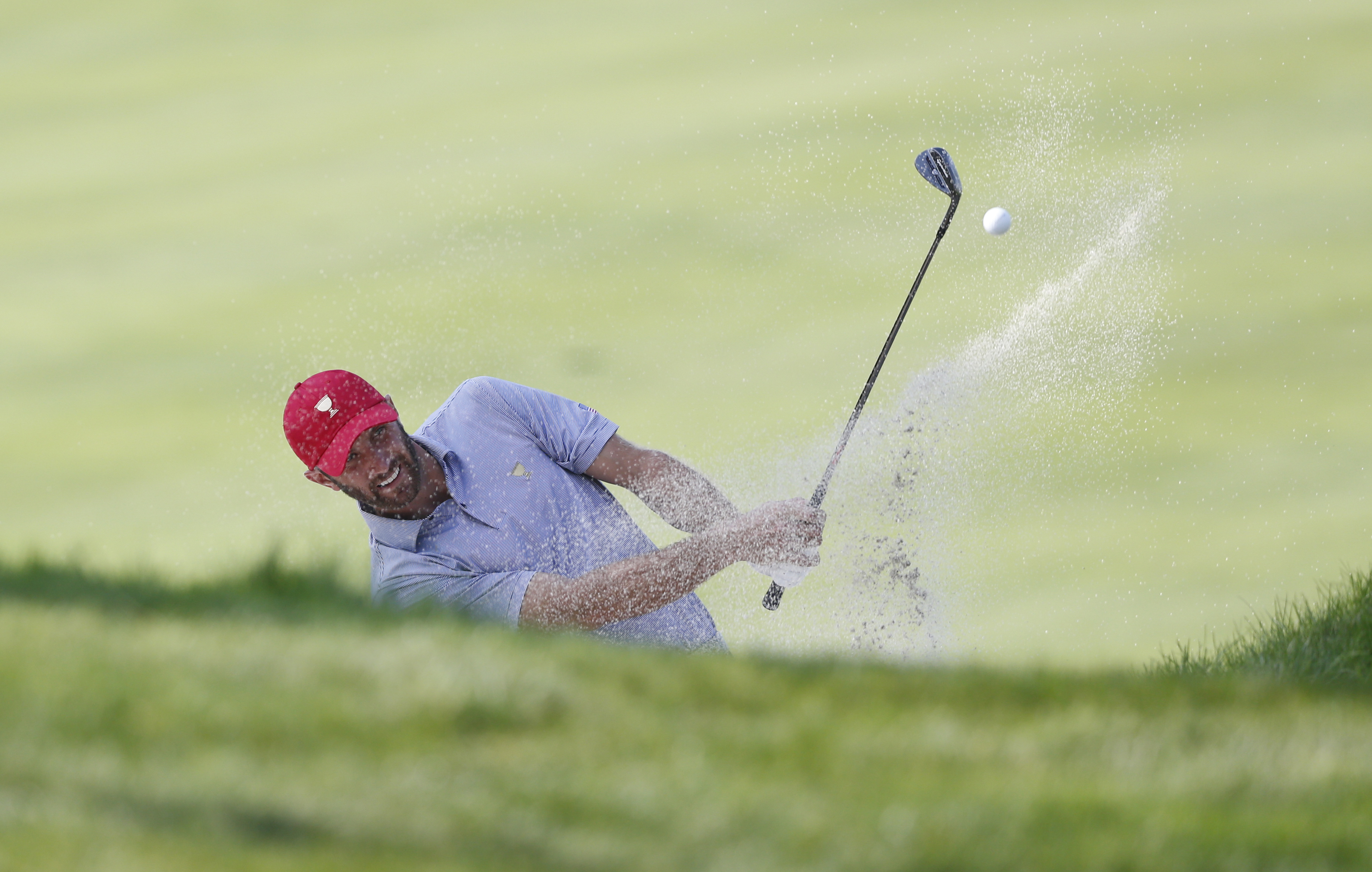 United States team player Dustin Johnson hits from a bunker on the third hole during a practice round ahead of the Presidents Cup golf tournament at Jack Nicklaus Golf Club Korea in Incheon, South Korea, Tuesday, Oct. 6, 2015. (AP Photo/Lee