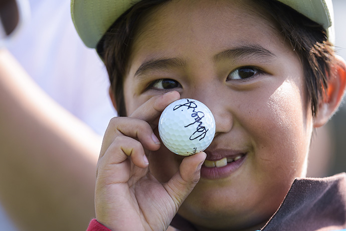 A young fan holds up a ball autographed by an International Team player on the 16th hole during practice for The Presidents Cup.