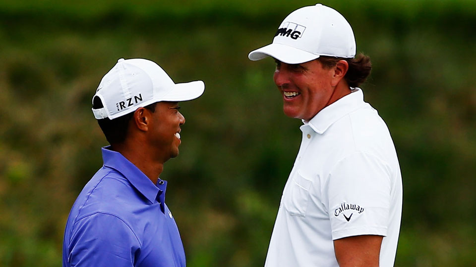 Tiger Woods and Phil Mickelson share a laugh during the first round of the 2014 PGA Championship.