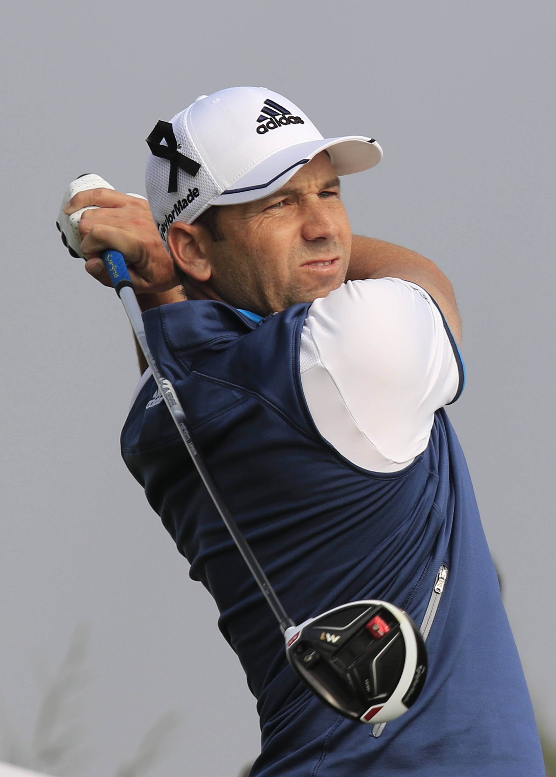 Sergio Garcia of Spain wearing a black ribbon on his hat to mourn for the victims killed in Friday's attacks in Paris, France, tees off on the 7th hole during the third round of the BMW Masters golf tournament at the Lake Malaren Golf Club in Shanghai,