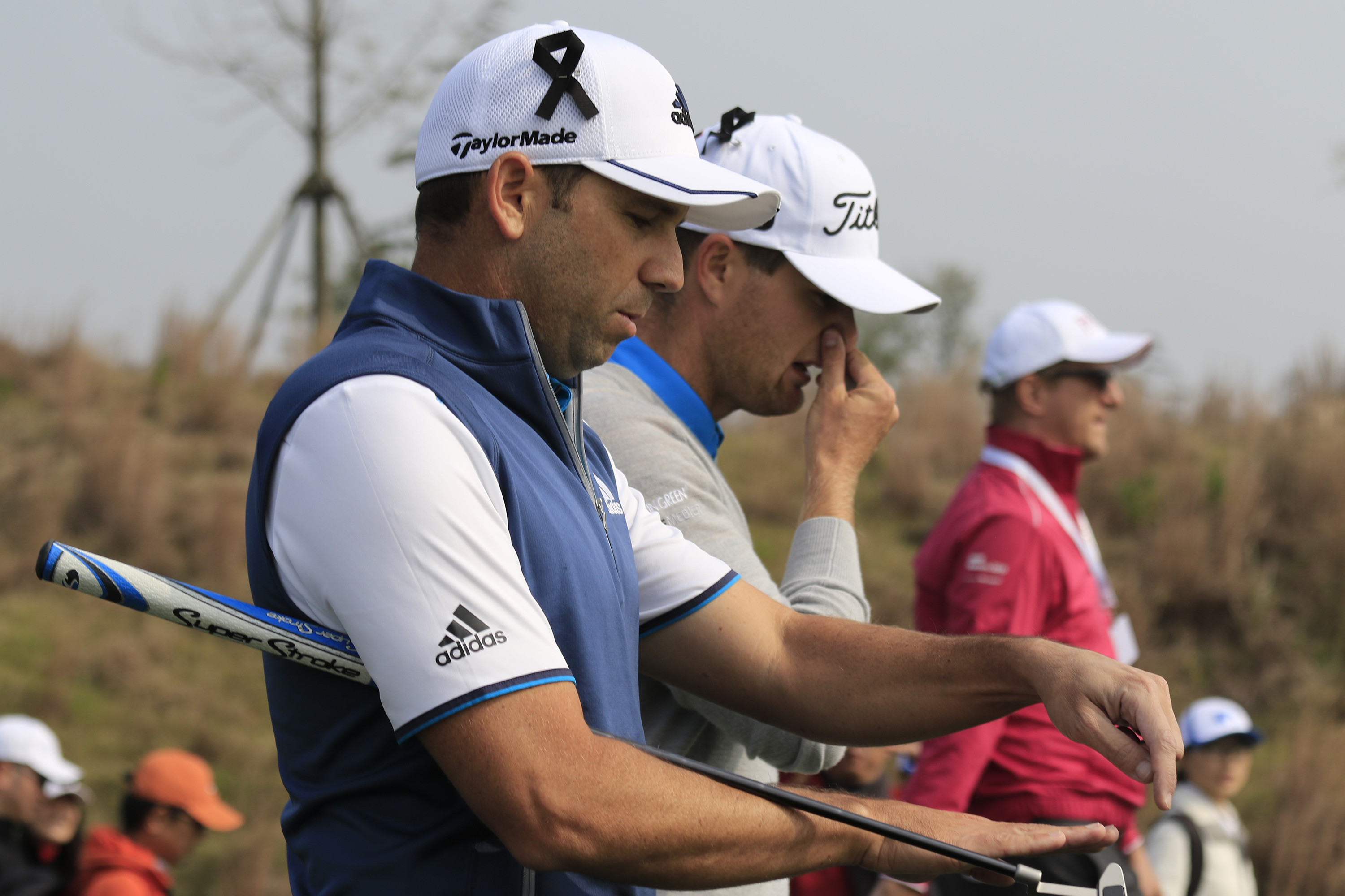 Sergio Garcia of Spain, left, and Lucas Bjerregaard of Denmark, center, both wear black ribbons on their hats to mourn for the victims killed in Friday's attacks in Paris, France.