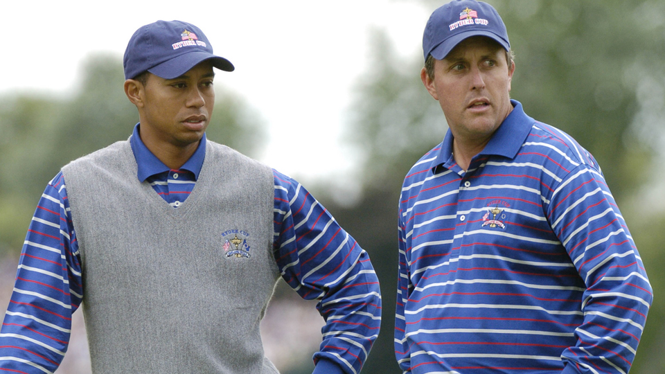 Tiger Woods and Phil Mickelson wait during their four-ball competition at the 2004 Ryder Cup in Detroit, Michigan, on Sept. 17, 2004.