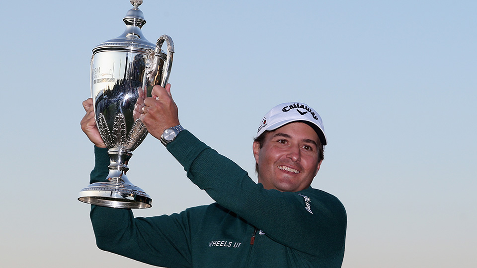 Kevin Kisner celebrates with the winner's trophy on the 18th green of the Seaside Course after winning The RSM Classic on November 22, 2015.