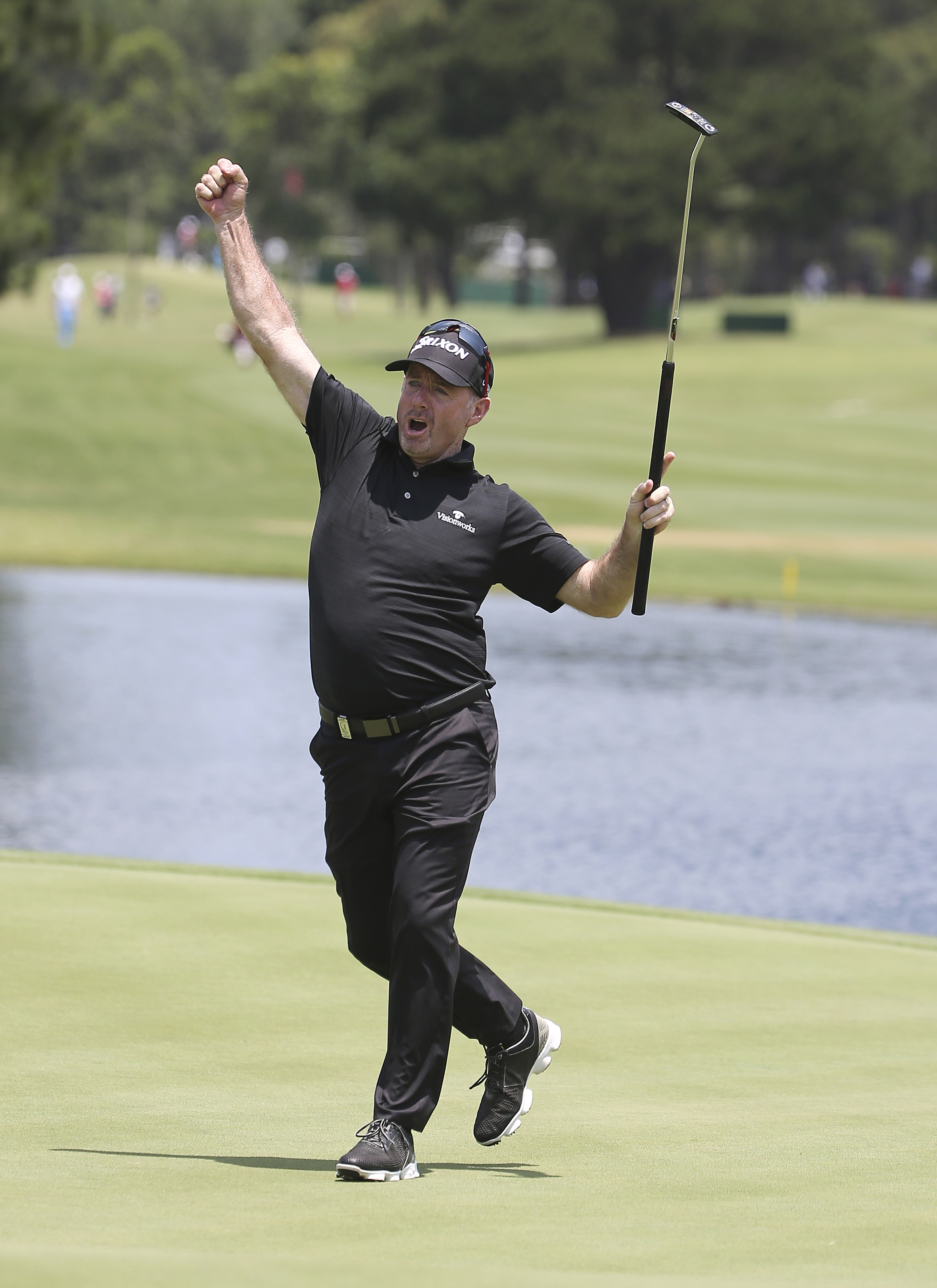 Rod Pampling of Australia pumps his fist as he celebrates an eagle on the 18th green on the final day of the Australian Open in Sydney Sunday, Nov. 29, 2015.