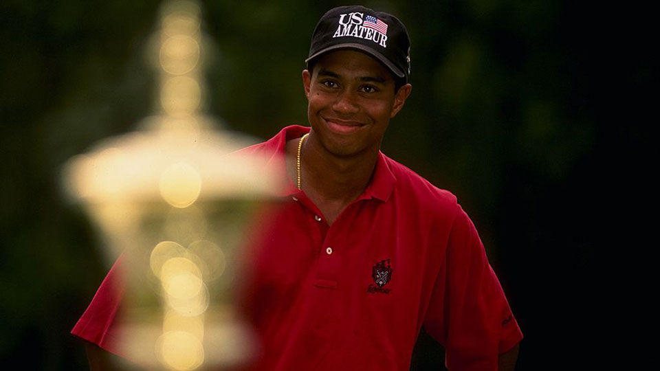 Tiger Woods looks at the winner's trophy after winning the 1996 U.S. Amateur Championship at Pumpkin Ridge Golf Course.